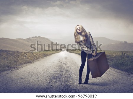 Beautiful woman carrying a suitcase with some difficulty on a countryside road - stock photo