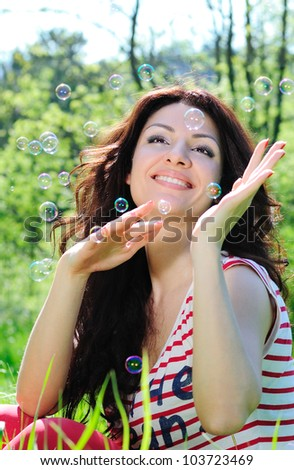 Beautiful woman catches soap bubbles on meadow - stock photo