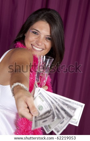beautiful woman celebrating the new year eve with champagne and lots of money - stock photo