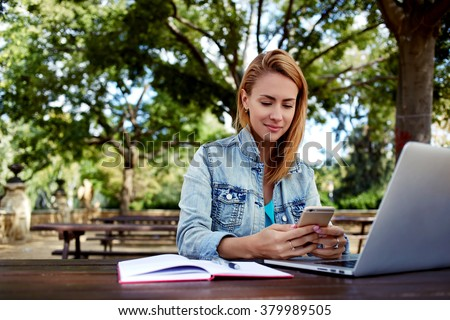 Beautiful woman chatting on mobile phone while sitting with portable laptop computer on campus, young female in good mood reading text message on cell telephone while resting after work on net-book  - stock photo