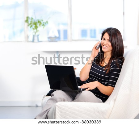 Beautiful woman chatting on the phone while surfing the internet - stock photo