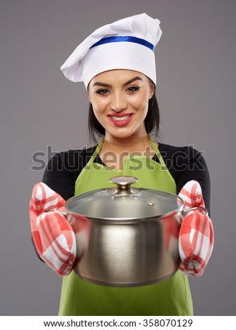 Beautiful woman chef offering a pot with hot food, ready to be eaten - stock photo