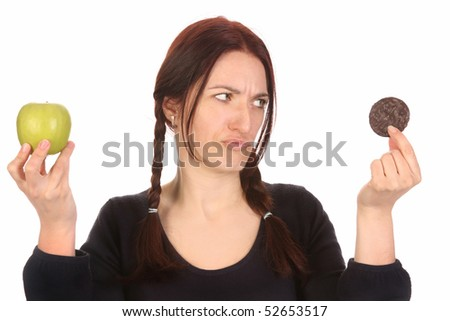 beautiful woman choosing between chocolate cookies and apple on white background - stock photo
