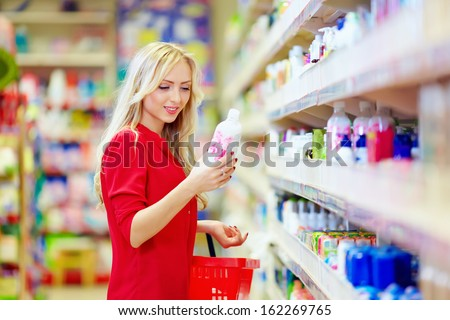 beautiful woman choosing personal care product in supermarket