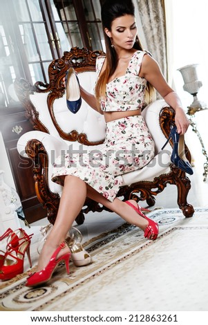 Beautiful woman choosing shoes in luxury home interior  - stock photo