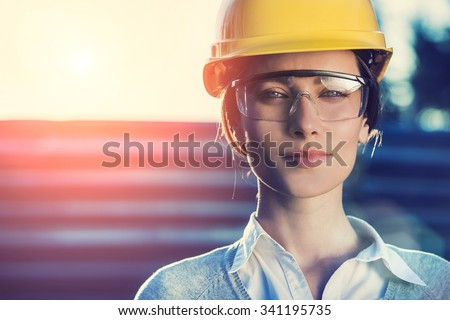 beautiful woman civil engineer close up portrait in front of a sunset background - stock photo