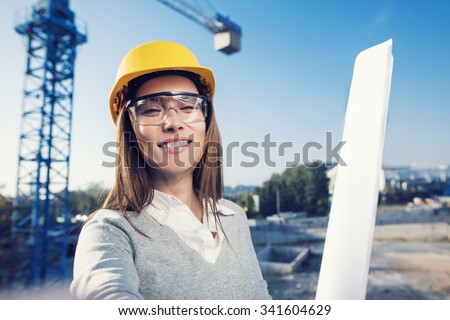 Beautiful woman civil engineer is taking a self portrait in her work in front of a crane - stock photo