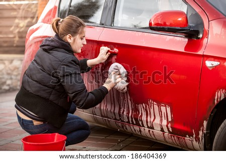 Beautiful woman cleaning car door from mud and dirt