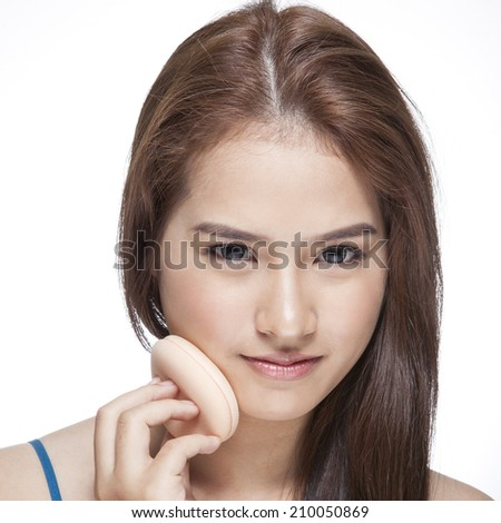 Beautiful woman cleaning her pretty face with cotton sponge - over white background - stock photo