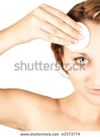 Beautiful woman cleaning her pretty face with cotton swab - stock photo