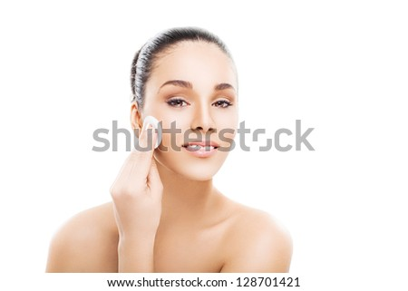 Beautiful woman cleaning her pretty face with cotton swab - over white background - stock photo
