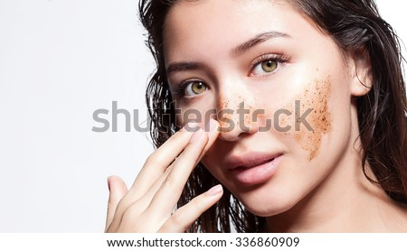 Beautiful woman cleans the skin scrub on a white background isolated - stock photo