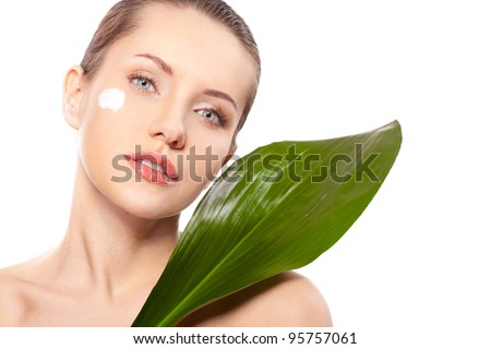beautiful woman closeup face portrait with green leaf and cream on face - stock photo