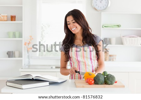 Beautiful woman consulting a notebook while cooking vegetables in the kitchen - stock photo