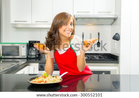 beautiful woman cooking in modern kitchen posing with carrots and plate of food on counter. - stock photo