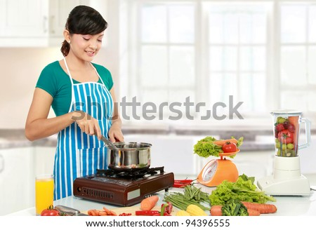 Beautiful woman cooking something in the kitchen - stock photo