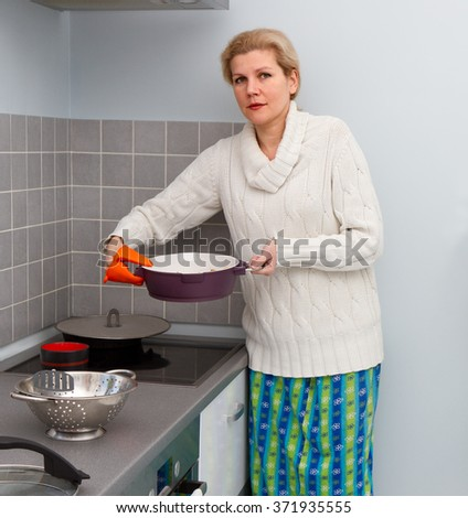 Beautiful woman cooking soup at stove in kitchen at home - stock photo