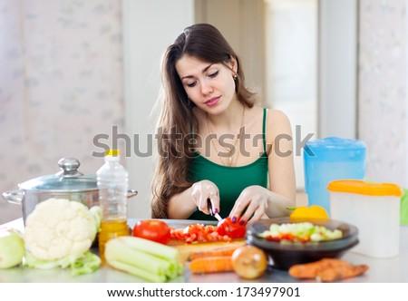 beautiful woman cooking vegetarian salad in  kitchen  - stock photo