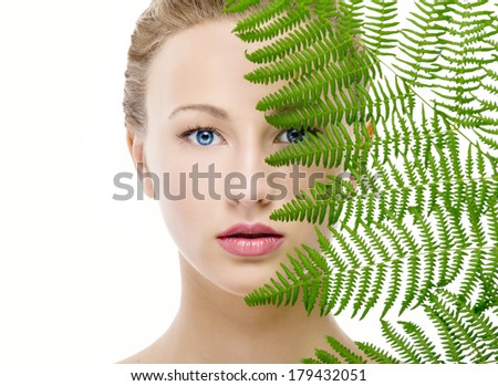 Beautiful woman covering her face with green leaves - stock photo