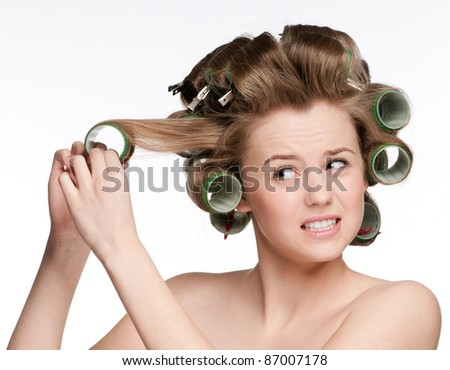 beautiful woman curling her hair with roller