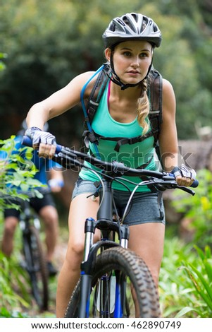 Beautiful woman cycling in forest