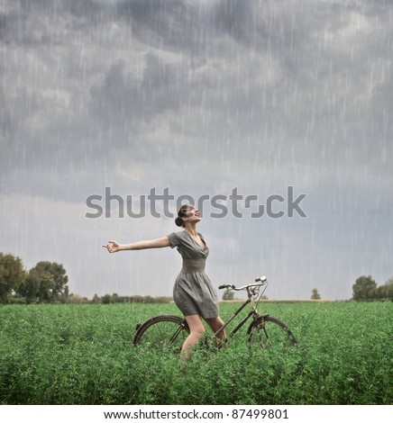 Beautiful woman cycling on a green meadow in the rain - stock photo