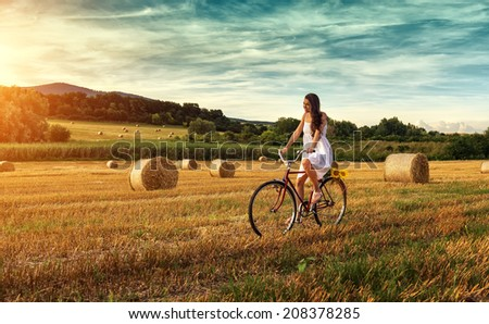 Beautiful woman cycling on an old red bike, in a wheat field - stock photo