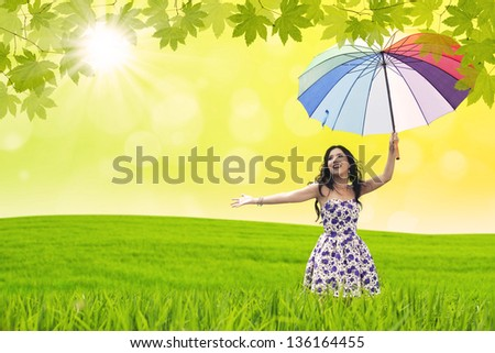Beautiful woman dance with umbrella in green field