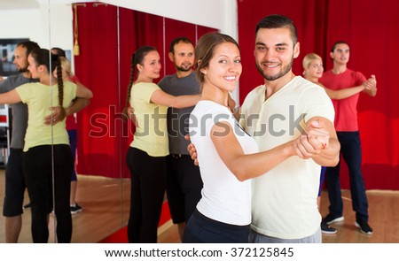 Beautiful woman dancing a slow dance with a handsome man in dancing studio with other dancing couples in background - stock photo