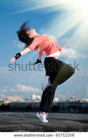 Beautiful woman dancing hip-hop modern style over urban city landscape, blue sky and sun - stock photo