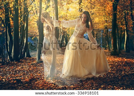Beautiful woman dancing in autumn woods. Surreal and romantic - stock photo