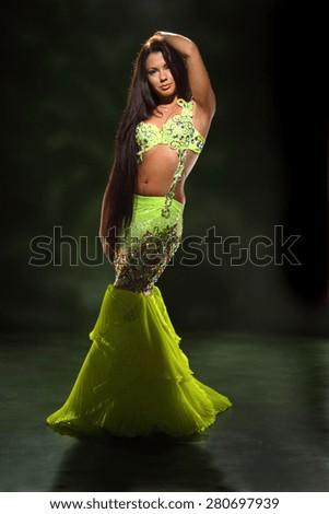 beautiful woman dancing in colorful Arabic dance costume. beautiful brunette. long hair. - stock photo
