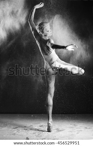 Beautiful woman dancing with flour in Studio on black background