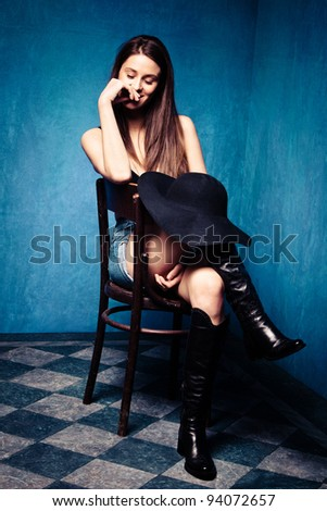 beautiful woman daydream, sit in old grunge room, small amount of grain added - stock photo