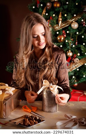 Beautiful woman decorating a Christmas present