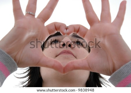 beautiful woman depicts the heart as hands over white background