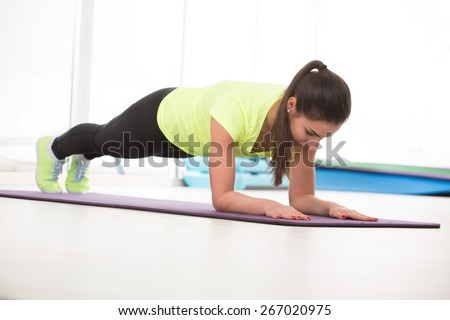 Beautiful woman do push ups in sport gym in yellow t-shirt on floor. - stock photo