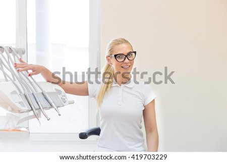 Beautiful woman doctor dentist in white costume posing at her working place near dental machine in glasses - stock photo