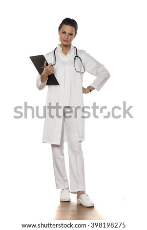 beautiful woman doctor in uniform posing with clipboard - stock photo