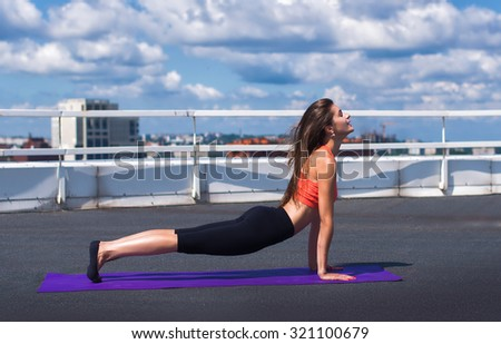 Beautiful woman doing a yoga exercise on he rooftop of a skyscraper - stock photo