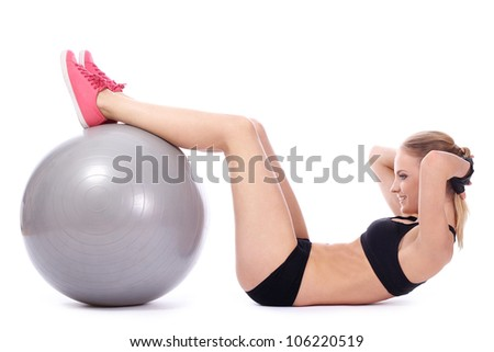 Beautiful woman doing abs exercises with fitness ball over white background - stock photo
