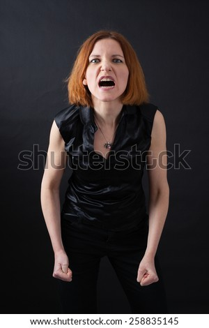Beautiful woman doing different expressions in different sets of clothes: angry - stock photo