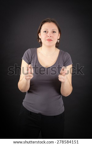 Beautiful woman doing different expressions in different sets of clothes: gun sign - stock photo