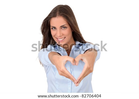 Beautiful woman doing heart shape with hands - stock photo