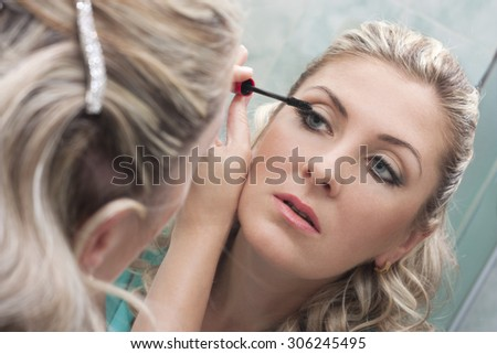 Beautiful woman doing make-up applying mascara to the eyelashes - stock photo
