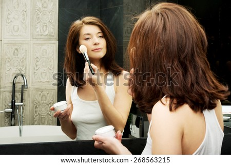 Beautiful woman doing make up in bathroom. - stock photo