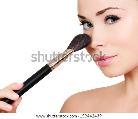 Beautiful woman doing make-up on face with cosmetic brush, isolated on white, copyspace  - stock photo