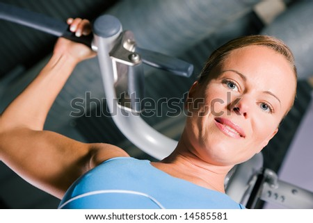 Beautiful woman doing pull-ups on a machine in the gym