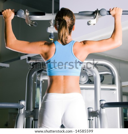 Beautiful woman doing pull-ups on a machine in the gym - stock photo
