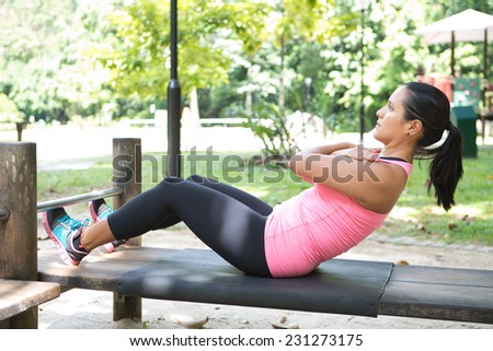 Beautiful woman doing sit ups on outdoor exercise park - stock photo